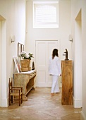 Woman walking down hallway with rustic wooden furniture