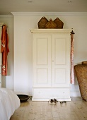 Wicker baskets on white-painted rustic wardrobe in plain bedroom