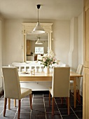 Chairs upholstered in white and wooden table on dark tiled floor