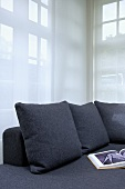 Grey sofa cushions to match sofa against transparent curtain in corner of living room