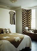 Brown and white throw on double bed and curtain on window