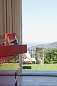 Blick neben rotem Sideboard auf die Terrasse und auf die Berglandschaft