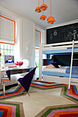 Bunk beds in children's bedroom with bright orange accents and one wall painted with black chalkboard paint