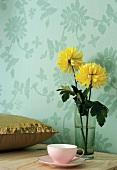 Gelbe Blumen in Trinkglas und Paillettenkissen vor Blumentapete
