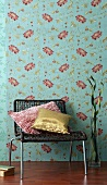 Low chair and decorative pillows in front of floral wallpaper