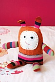 Hand-made rag doll in striped fabric with long ears and embroidered felt face