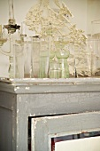 Collection of antique glass vases on shabby chic cupboard