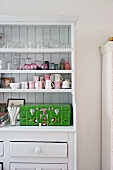 Glasses, cups and painted wooden case on white-painted kitchen dresser