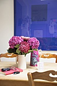 Pink and violet bouquet in white ceramic jug on wooden table in front of blue painting on wall