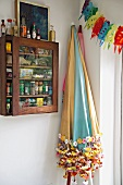 Colourful parasols and spice cabinet on wall in corner of kitchen