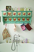 Painted, wall-mounted rack with flower motif and collection of antique bottles above vintage-style bathtub tap fittings