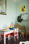 Pink children's chairs and table next to antique rocking horse in child's bedroom