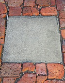 Square concrete block combined with uneven brick pavement