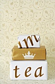 Stacked presents in creative gift wrap in front of wall paper