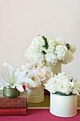 Various white flowers in white tins and two old books on striped tablecloth