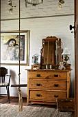 Antike Holzkommode mit Spiegel vor Backsteinwand