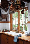 Rustic kitchen with hanging copper pots and cooking utensils