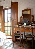 Antique dressing table and wooden chairs in a rustic bedroom