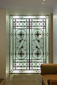 Backlit, floor-to-ceiling glass element with Art Deco geometric pattern