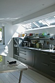 Kitchen counter with grey cupboard doors below skylight in designer kitchen