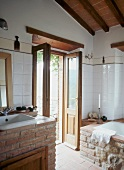 Brick-built washstand and bathtub in modernised bathroom with open terrace door