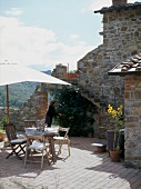 Dining area with parasol on Mediterranean terrace against old stone walls