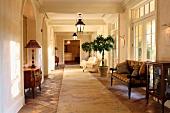 Antike Möbel im grosszügigen Vorraum mit altem Terrakottaboden in mediterraner Villa