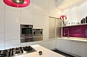 Designer kitchen with gas hob built into kitchen island and white cupboard doors