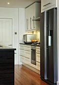 Corner of designer kitchen with white cupboard doors and stainless steel, upright fridge