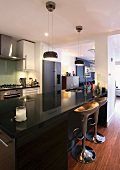 Designer kitchen counter with glossy black work surface and bar stools in open-plan kitchen