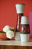 Vasenset im 70er Jahre Stil und weisse Nelken in Schale vor rot getönter Wand