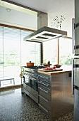 Küchenblock im Edelstahllook mit Dunstabzug vor Terrassenfenster