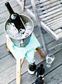 Flasche Rotwein in Kühler mit Eis auf Hocker auf Verande