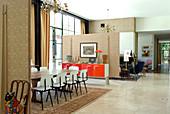 Tisch und Stühle im Fiftiesstil in offenem Ess- und Wohnbereich durch Raumteiler getrennt in klassisch modernem Haus