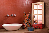 Wash basin on concrete surface against red wall