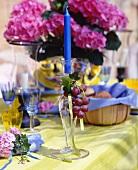 Sommerlich gedeckter Tisch mit Trauben-Deko und Hortensien