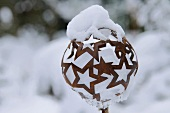 Ball made of rusty metal stars topped and filled with snow