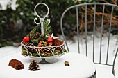 Metal cake stand with natural decorations and baubles on snowy garden table