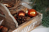 Wooden crate with pine cones and Christmas tree baubles