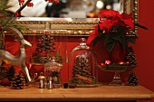 Fir cones under glass cloches, miniature tin rocking horse and poinsettias as Christmas decorations