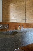 Wash basin hollowed out of stone block below designer wall-mounted tap and mirror