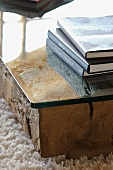 Stack of books on low table made of glass top on wooden block