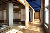 Meditation room with open, Japanese-style sliding wall panels in industrial hall with blue-painted ceiling