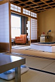 Open sliding wall panel with view into Japanese-style bedroom