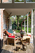 Rustic wooden chairs with colourful cushions and furs on a covered wooden terrace with antique steel chairs