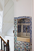 A hallway with an antique coloured wooden banister and an old wash basin in a wall niche with historic Delft tiles