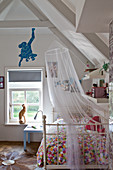 A wrought iron bed with a colourful bedspread and a mosquito net in a child's bedroom with a blue monkey cut out of wall paper above the window