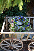 Wreath of gentian flowers and cushion bush sprigs on pewter can in handcart