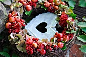Vine wreath with rosehips and a metal heart