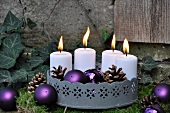 Festive garden decoration: zinc tray with candles on bed of moss